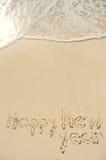 Feliz Año Nuevo escrita en arena en la playa Foto de archivo libre de regalías