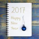 Feliz Año Nuevo 2017 escrita en cuaderno y chuchería de la Navidad Fotos de archivo