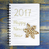 Feliz Año Nuevo 2017 escrita en cuaderno y pan de jengibre de la Navidad Imágenes de archivo libres de regalías