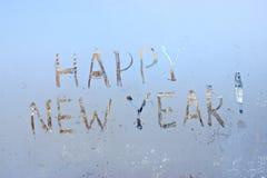 Feliz Año Nuevo escrita en fondo escarchado de la ventana del invierno Fotografía de archivo