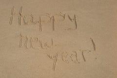 Feliz Año Nuevo escrita en la arena Imágenes de archivo libres de regalías