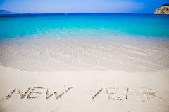 Feliz Año Nuevo escrita en la arena blanca Imágenes de archivo libres de regalías