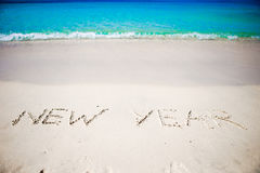 Feliz Año Nuevo escrita en la arena blanca Foto de archivo