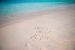 Feliz Año Nuevo escrita en la arena blanca Imagen de archivo