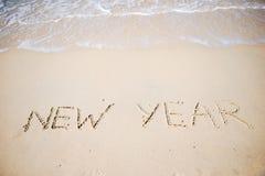 Feliz Año Nuevo escrita en la arena blanca Fotos de archivo