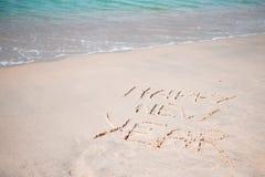 Feliz Año Nuevo escrita en la arena blanca Fotografía de archivo libre de regalías