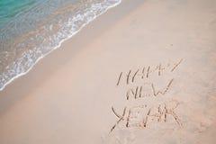 Feliz Año Nuevo escrita en la arena blanca Imagen de archivo libre de regalías