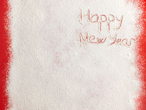Feliz Año Nuevo escrita en la nieve blanca Imagen de archivo