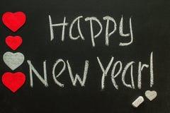 Feliz Año Nuevo escrita en la pizarra con los corazones Fotografía de archivo libre de regalías