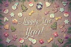 ¡Feliz Año Nuevo! Escrito entre las galletas del pan de jengibre y las ramas del abeto fotos de archivo