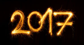 Feliz Año Nuevo hecha por las bengalas en fondo negro Fotos de archivo libres de regalías