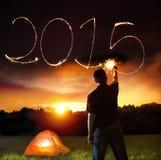 Feliz Año Nuevo 2015 hombre joven que dibuja 2015 por el palillo chispeante Fotografía de archivo libre de regalías