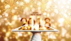 Feliz Año Nuevo 2018, mano que sostiene la tableta digital con el fondo de lujo de los fuegos artificiales de Bokeh del oro Imagenes de archivo