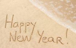 Feliz Año Nuevo manuscrita en la arena Fotos de archivo libres de regalías