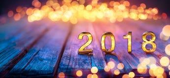 2018 - Feliz Año Nuevo - números de oro en la tabla Defocused Fotografía de archivo