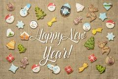 ¡Feliz Año Nuevo! Saludo del día de fiesta escrito entre las galletas decorativas del pan de jengibre Fotografía de archivo