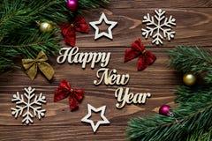 Feliz Año Nuevo Título pedido con la decoración en el fondo de madera con los arcos de la cinta, las bolas de la Navidad, copos d Fotos de archivo libres de regalías