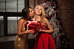 Feliz Año Nuevo a usted dos mujeres jovenes hermosas en una Navidad de la celebración con presentes y kisess Partido del ` s del  Fotos de archivo libres de regalías