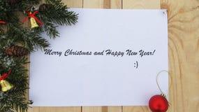 Feliz Año Nuevo y Feliz Navidad en el papel, el tablero del fondo, el árbol de navidad y decoraciones Fotografía de archivo