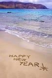 Feliz Año Nuevo y signo de exclamación escritos en la arena Foto de archivo
