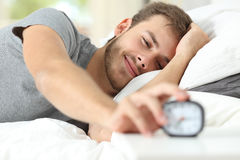 Feliz acorde de um homem feliz que para o despertador Fotografia de Stock Royalty Free