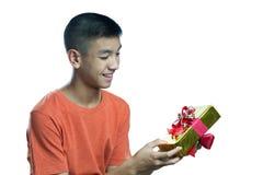 Feliz adolescente asiático joven de conseguir un presente Imagenes de archivo