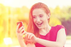 Feliz, alegre, muchacha, el mandar un SMS emocionado en el teléfono celular Imagen de archivo libre de regalías