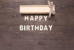 Feliz aniversario e caixa de presente no fundo de madeira com espaço da cópia Imagem de Stock Royalty Free