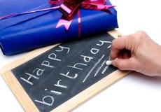 Feliz aniversario escrito em um quadro-negro da ardósia com um presente Fotos de Stock Royalty Free