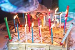 Feliz aniversario escrito em velas do Lit no bolo colorido Mão que sustenta aquela que ilumina uma vela no bolo ilustração stock