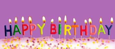 Feliz aniversario iluminado velas no fundo roxo Imagens de Stock
