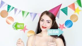 Feliz aniversario A menina engraçada em sorrisos festivos cor-de-rosa e em guardar de um tampão um sinal do partido Retrato de um vídeos de arquivo
