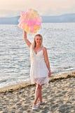 Feliz aniversario! Mulher feliz de sorriso dos jovens com os balões coloridos na praia que comemora seu aniversário imagens de stock