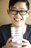 Feliz asiático joven con el vidrio de leche Fotos de archivo libres de regalías
