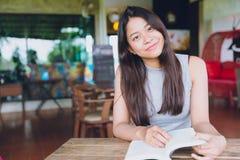 Feliz bonito bonito adolescente asiático do livro de leitura do sorriso fotografia de stock royalty free