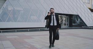 Feliz, carismático, joven, negocio, hombre, viene, hacia fuera, de, la oficina, edificio, hablando, teléfono, tenencia, la suya,