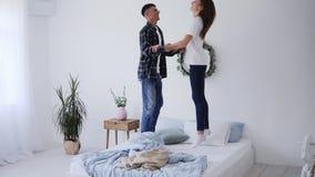 Feliz casal de família engraçada pulando em colchão de cama, marido e mulher ativa e sem carinho se divertindo rindo e se diverti filme