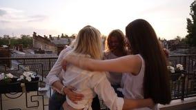 Feliz, chicas jóvenes abrazadas en el círculo, vista lateral Seis muchachas atractivas abrazo, mirándose, colocándose al aire lib almacen de metraje de vídeo