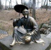 Feliz chino de la escultura con un paraguas arboretum Foto de archivo