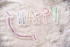Feliz con una sonrisa escrita en una playa arenosa Fotos de archivo libres de regalías