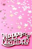 Feliz cumpleaños de la inscripción de madera en un fondo rosado imagen de archivo