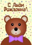 Feliz cumpleaños de la postal en ruso Oso divertido con un arco, estrellas Imagenes de archivo