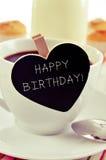 Feliz cumpleaños del desayuno y del texto en una pizarra en forma de corazón Imágenes de archivo libres de regalías