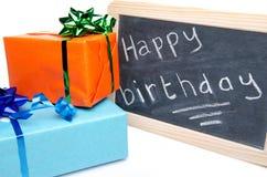 Feliz cumpleaños escrito en una pizarra de la pizarra con los regalos Fotos de archivo
