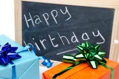 Feliz cumpleaños escrito en una pizarra de la pizarra con los regalos Imagenes de archivo