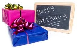 Feliz cumpleaños escrito en una pizarra de la pizarra con los regalos Imagen de archivo libre de regalías