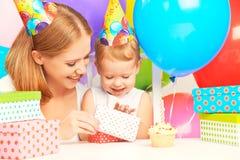 Feliz cumpleaños mime a dar el regalo a su pequeña hija con los globos Fotografía de archivo