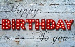 Feliz cumpleaños que brilla intensamente en fondo de madera Imágenes de archivo libres de regalías