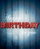 Feliz cumpleaños que brilla intensamente en fondo de madera Imagen de archivo libre de regalías
