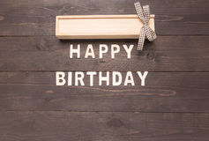 Feliz cumpleaños y caja de regalo en fondo de madera con el espacio de la copia Imagen de archivo libre de regalías